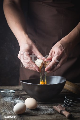 Professional chef hands are breaking an egg into bowl to make dough on wooden table, over dark background