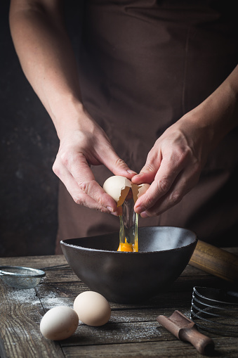 istock hands are breaking an egg 1192899584