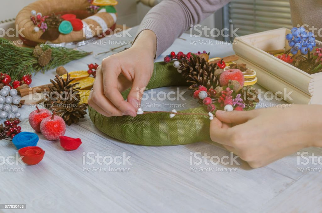 Hands are creating Christmas wreath and ribbon bow on a wooden board background. stock photo