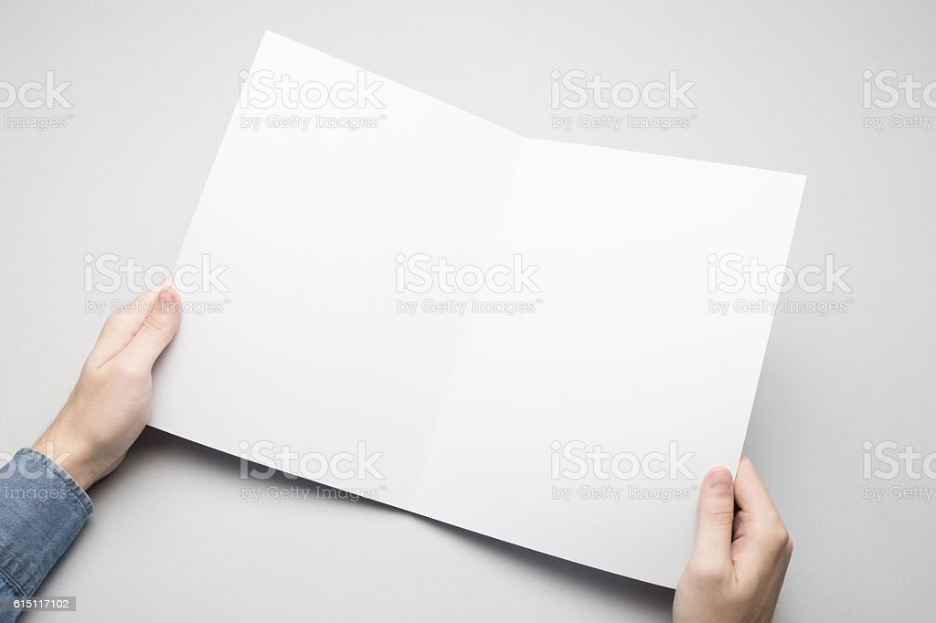 hands are holding a a4 bifold white paper poster stock photo more