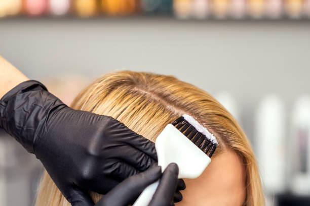 handen schilderen het vrouwelijke haar in een witte kleur close-up. - gekleurd haar stockfoto's en -beelden