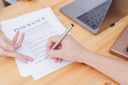 istock Hands are signing insurance contract.Contract agreement policy concept. 965545114