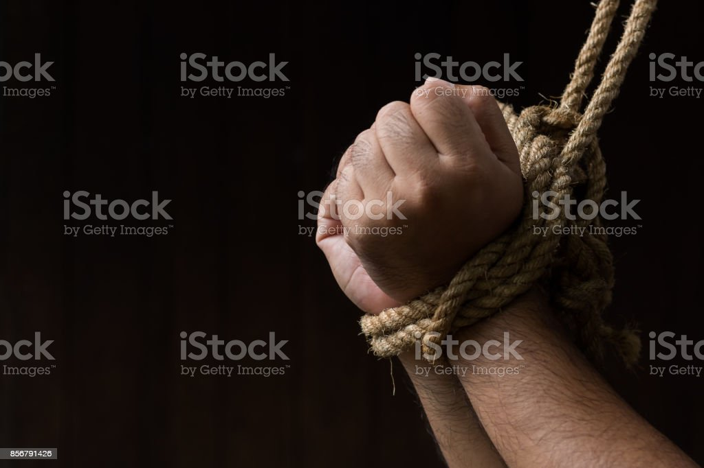 Hands are tied with rope On the black background / loss of freedom and human rights stock photo