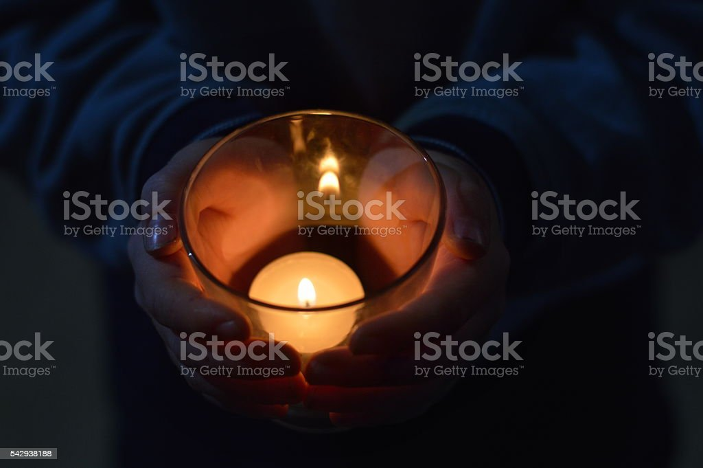hands around a burning candle stock photo