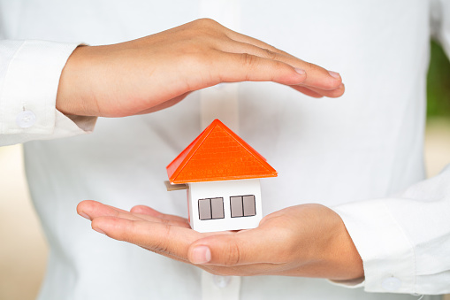 istock Hands as a protecting roof over a little house, Property insurance and security concept. Protecting gesture of man and symbol of house,  Invesment and Risk Management. 1153549737
