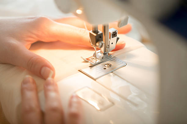 hands at sewing machine - hutmacher stock-fotos und bilder