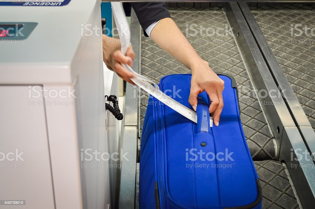 hands attaches a luggage tag to suitcase stock photo