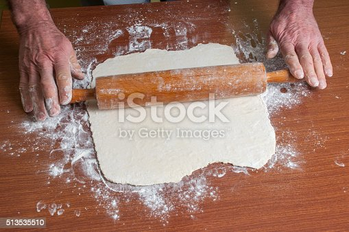 673400318istockphoto Hands baking dough with rolling pin on table 513535510
