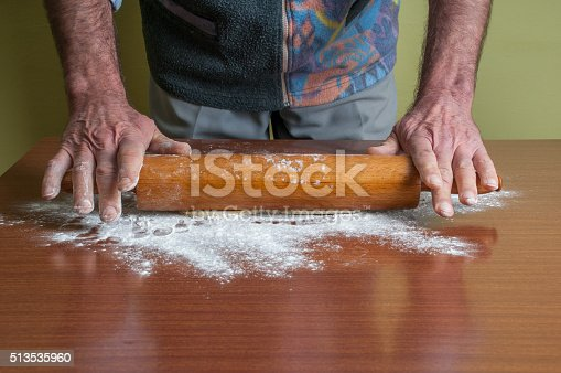 673400318istockphoto Hands baking dough with rolling pin on table 513535960