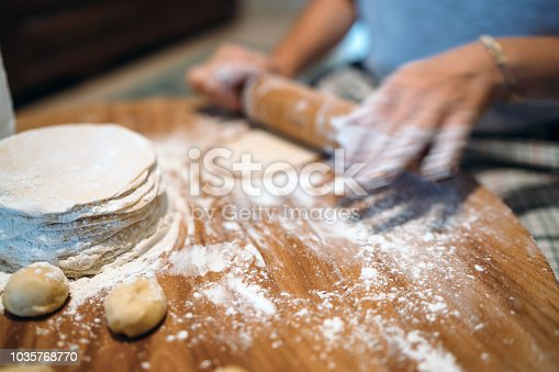 673400318istockphoto Hands baking dough with rolling pin on wooden table 1035768770