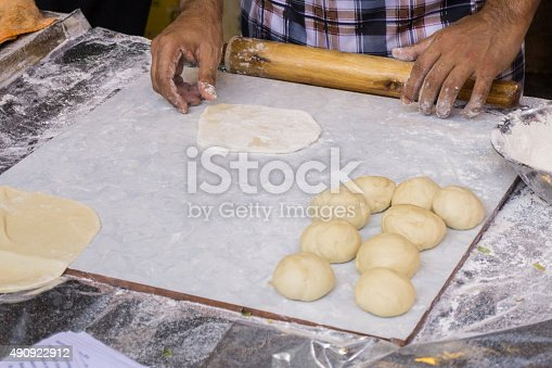 673400318 istock photo Hands baking dough with rolling pin on wooden table 490922912
