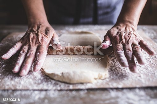 istock Hands baking dough with rolling pin on wooden table 673400318