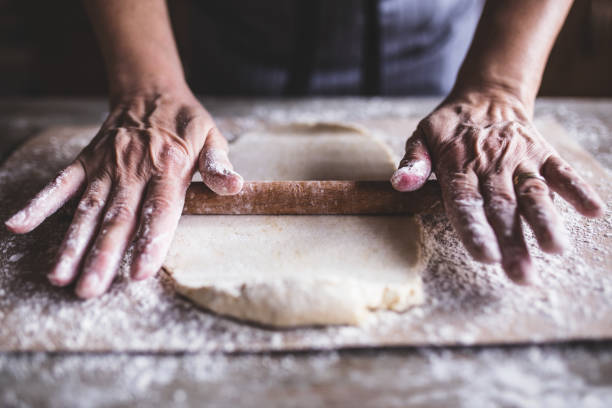 Hands baking dough with rolling pin on wooden table stock photo