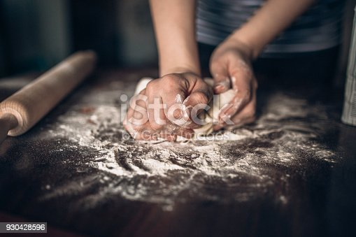 673400318istockphoto Hands baking dough with rolling pin on wooden table 930428596