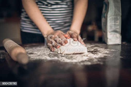 673400318istockphoto Hands baking dough with rolling pin on wooden table 930428780