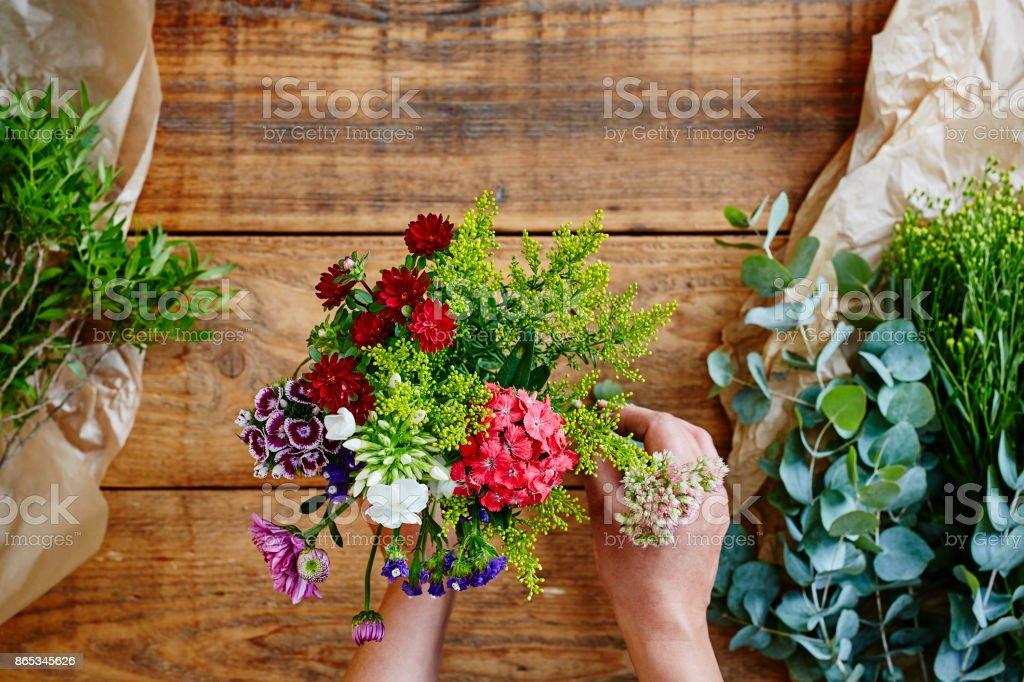 hands binding a wild flower bouquet flowershop stock photo