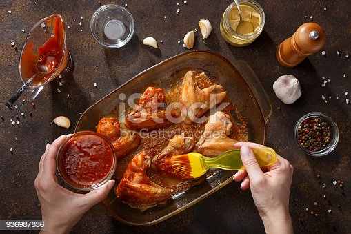 istock Hands brush baked wings with the bbq souce. 936987836