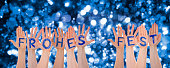 istock Hands Building Frohes Fest Means Merry Christmas, Glittering, Bokeh Background 1068984770
