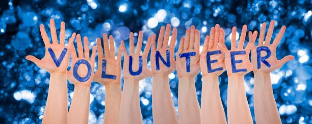 Hände-Gebäude Wort Freiwilligen, glitzernden und funkelnden Bokeh Hintergrund – Foto
