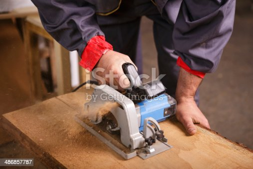 istock Hands carpenter working with a circular saw 486857787