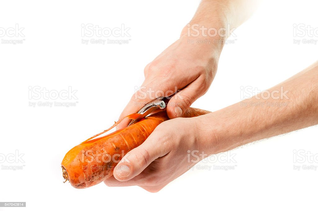 Hands carrots cleanse the skin with a knife stock photo