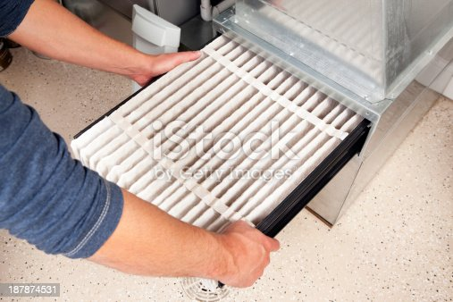 Male hands are installing a furnace air filter. This filter is not brand new but it is relatively clean, it was removed for inspection. This would be a typical filter style found in a high end newer house. The floor is epoxy painted concrete with traction chips and a floor drain.