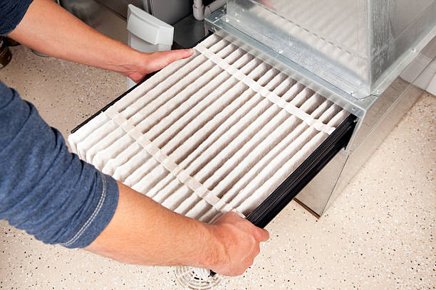 Hands Changing Furnace Air Filter Male hands are installing a furnace air filter. This filter is not brand new but it is relatively clean, it was removed for inspection. This would be a typical filter style found in a high end newer house. The floor is epoxy painted concrete with traction chips and a floor drain. air filter stock pictures, royalty-free photos & images
