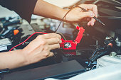 istock Hands check battery car mechanic working in auto repair service 880745180