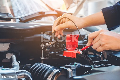 istock Hands check battery car mechanic working in auto repair service 880745324