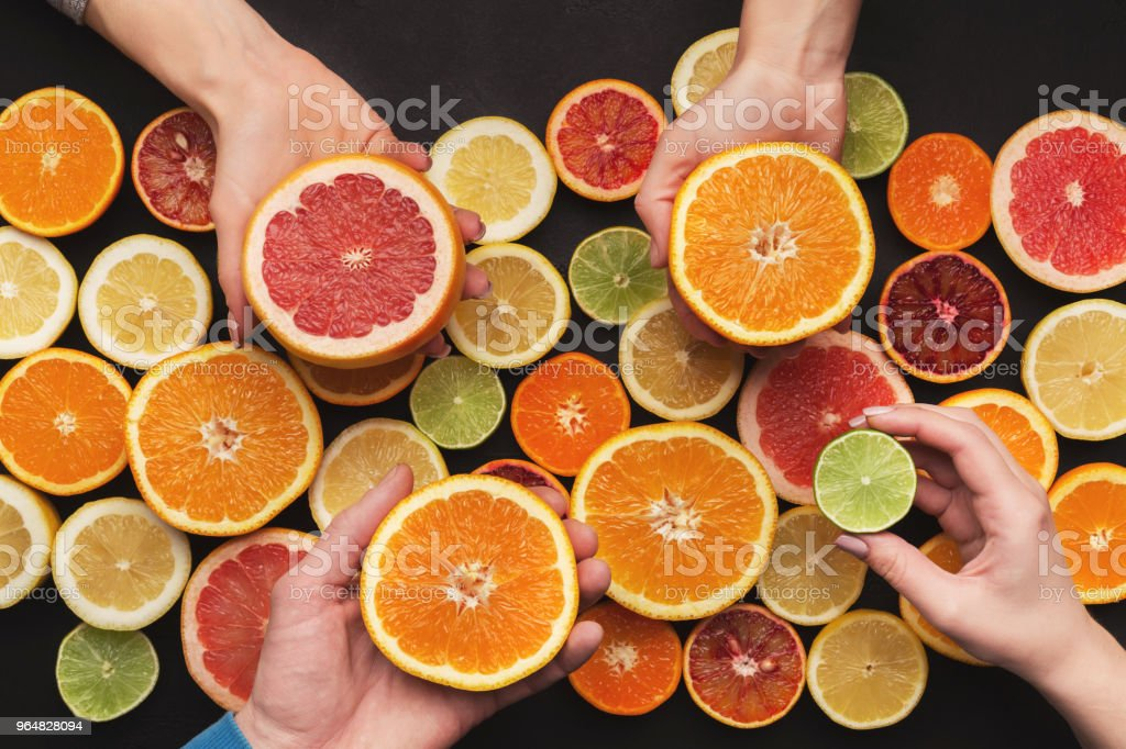 Hands choosing citrus fruits, top view royalty-free stock photo