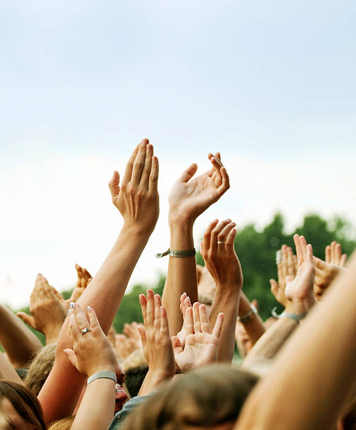 Hands Clapping in Crown Outdoors Large party group of people holding their arms and hands high in the air during an Outdoor Concert wristband stock pictures, royalty-free photos & images
