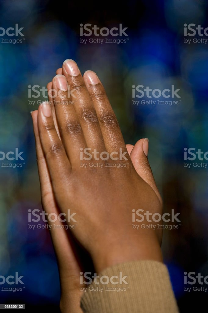 Hands clasped of person praying in church stock photo