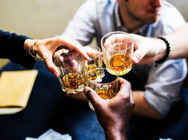 hands clinging alcohol drink glasses - whiskey stock photos and pictures