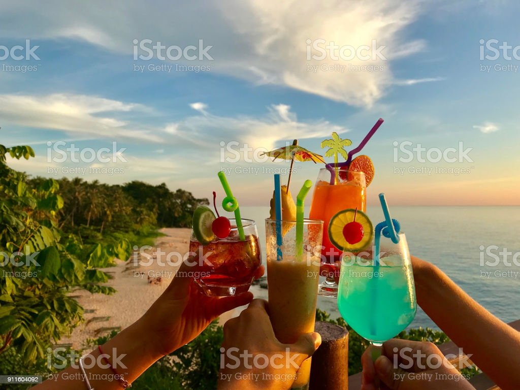 Hands Clinking With Cocktails Glasses Over Beach, Sea And Sky Background, Summer Tropical Vacation stock photo