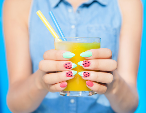 Hands close up of young woman with watermelon manicure