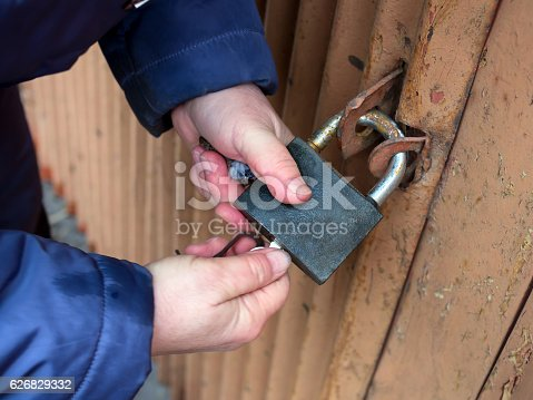 Hands closed padlock key on the gate