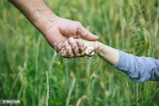 istock Hands closeup of a small child and an elderly person to stay together 976652486