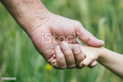 istock Hands closeup of a small child and an elderly person to stay together 976652546