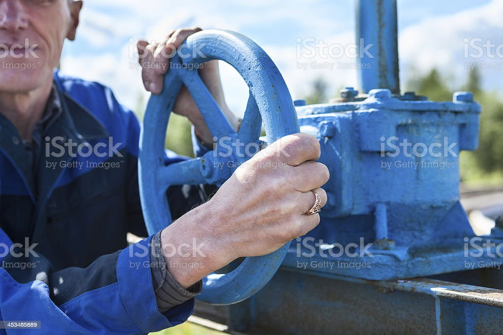 Hands close-up of senior manual worker turning cut-off valve stock photo