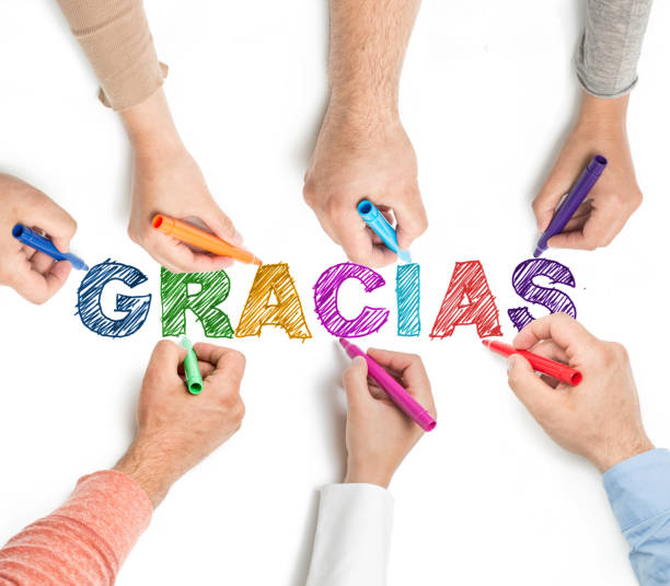"""Hands coloring word """"Gracias"""" on whiteboard. stock photo"""