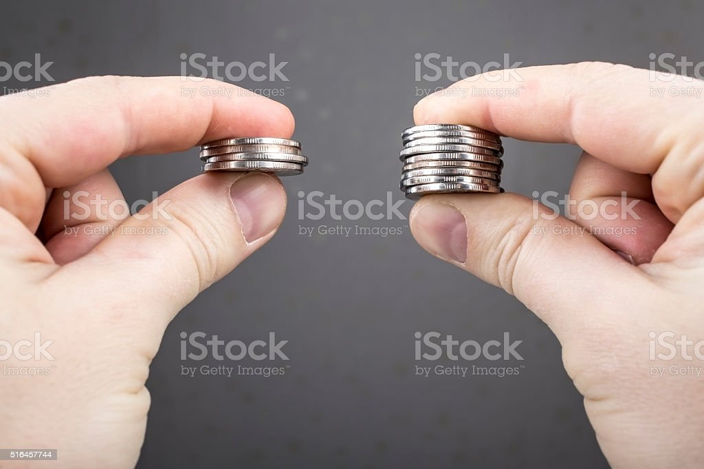 Hands compare two piles of coins of different sizes stock photo