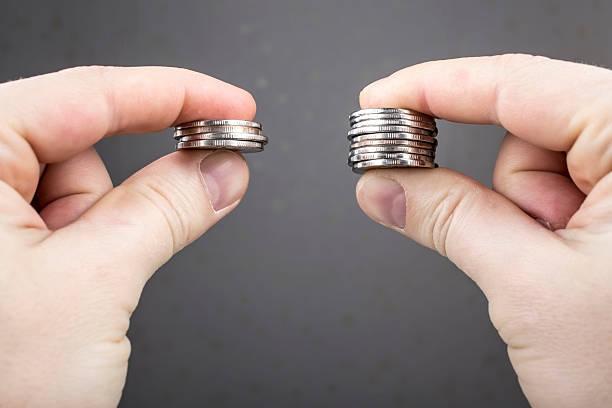 Mãos comparar duas pilhas de moedas de diferentes tamanhos - foto de acervo