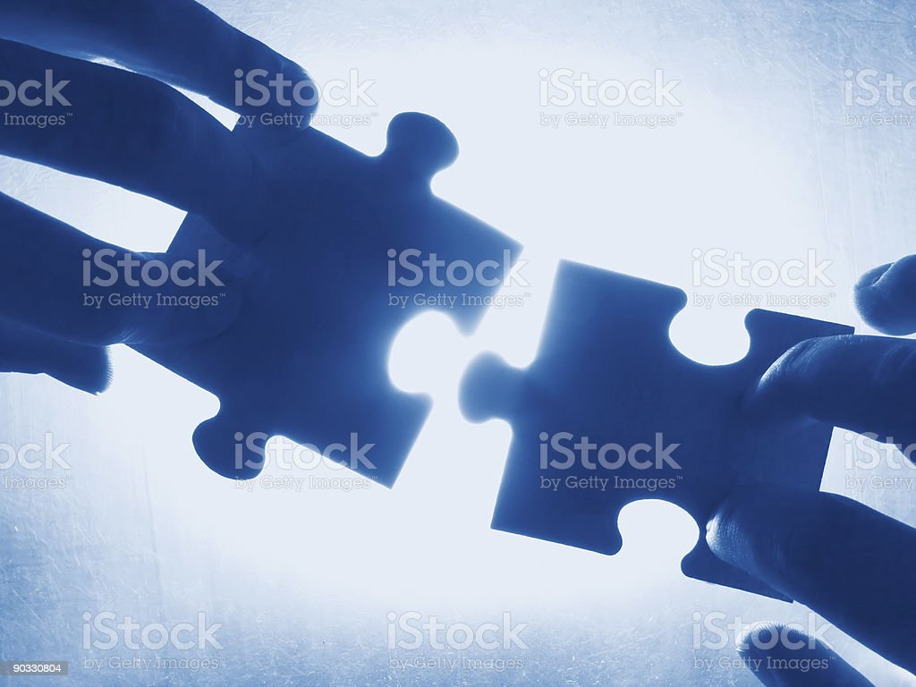 Hands connecting two blue puzzle pieces stock photo