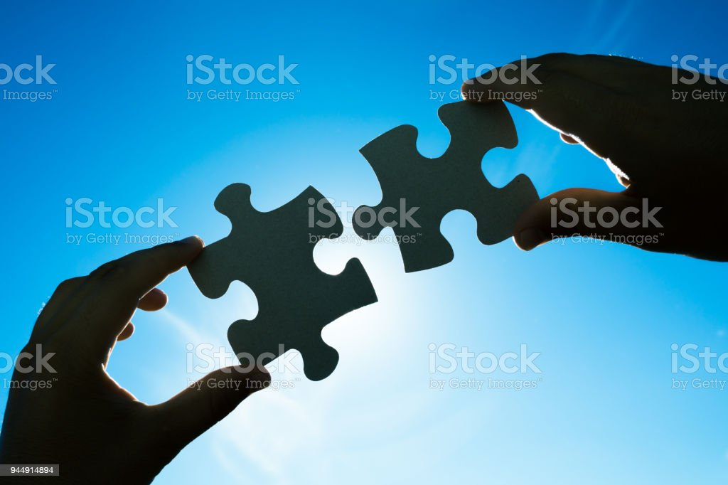Hands connecting two puzzle pieces stock photo