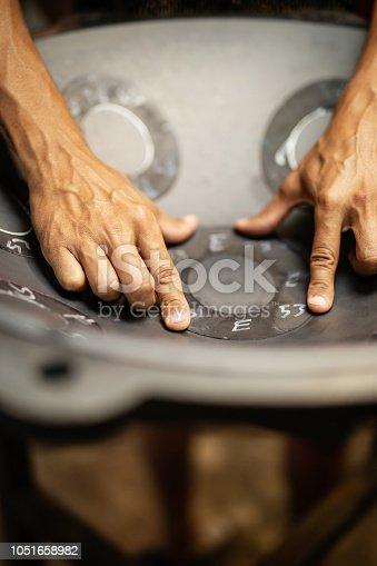 Artisan hands designing Handpan in his workshop, a metal percussion instrument.
