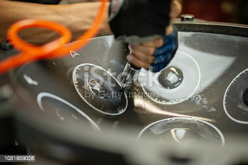 Artisan in his workshop using air hammer to construct a handpan, metal percussion instrument.