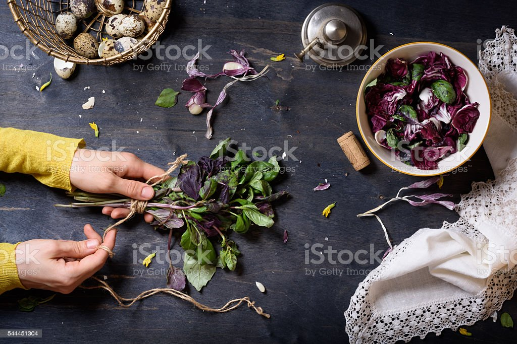 Hands cooking salad with fresh basil, radicchio and eggs. – Foto