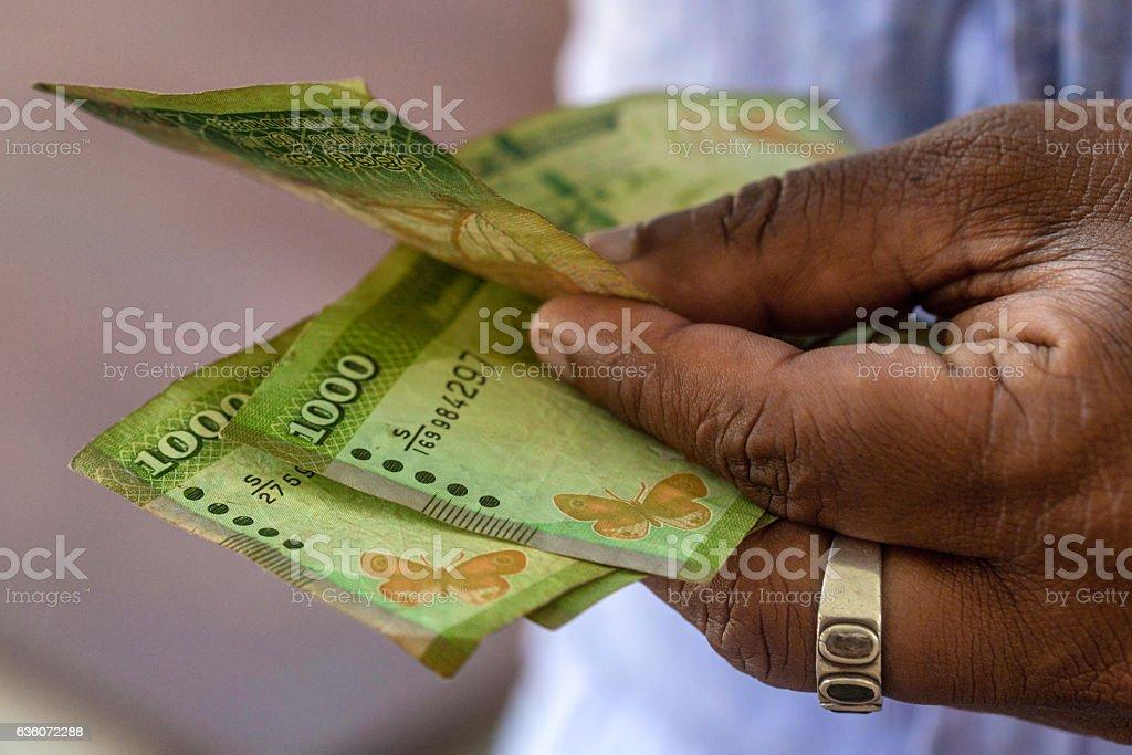 Hands counting srilankan rupies stock photo
