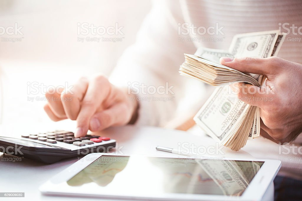 Hands counting us dollars with calculator and digital tablet stock photo