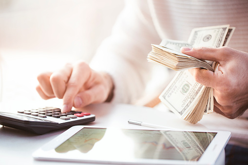 Hands Counting Us Dollars With Calculator And Digital Tablet Stock Photo - Download Image Now